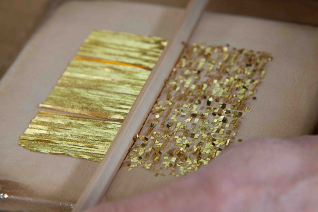 Gold and silver foil is cut into squats with a knife made by bamboo