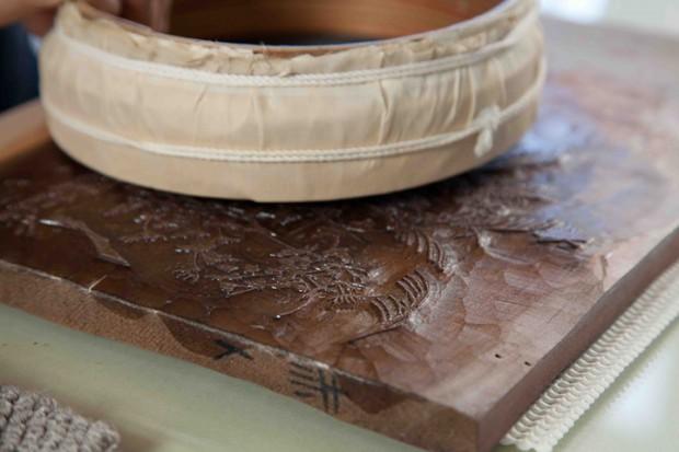 膠とフノリで解いた雲母の粉を木版にタンポを使ってむらにならないように付けます